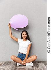 브루넷의 사람, 여자, 입는 것, 캐쥬얼한 옷, 보유, 공백, balloon, 와, copyspace, 동안, 마루에 앉아 있는 것, 와, 교차하는다리, 고립된, 위의, 회색의 배경