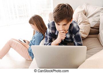 사진, 의, 2, 코카서스 사람, 키드 구두, 형제와 여동생, 8-10, 위에 휴식하는, 소파, 집의, 동안, 을 사용하여, smartphone, 와..., 휴대용 퍼스널 컴퓨터