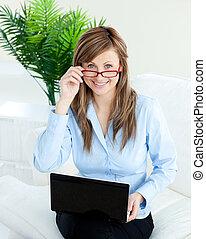 세련시키는, 여자 실업가, 을 사용하여, a, 휴대용 퍼스널 컴퓨터, 미소, 에, 그만큼, 카메라, 착석, 통하고 있는, a, 소파, 에서, 사무실