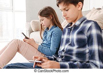 심상, 의, 2, 코카서스 사람, 키드 구두, 소녀, 와..., 소년 착석, 통하고 있는, 바닥, 공간으로 가까이, 소파, 집의, 와..., 양쪽, 을 사용하여, 휴대 전화