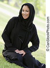 앉아 있고 있는 여성, 옥외, park에게서, 미소, (selective, focus)