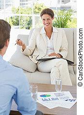 여자 실업가, 미소, 에, 동료, 소파에 앉아 있는 것