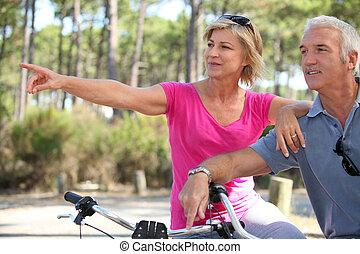 연장자 한 쌍, 자전거를 타는 것, 공원안에