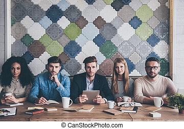 완전한, team., 젊은이의그룹, 사진기를 보는, 동안, 착석, 사무실에, 테이블, 통하고 있는, 비즈니스 회의