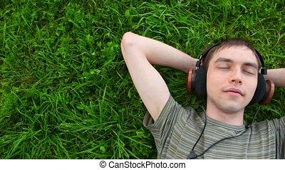 젊은이, 듣다, 음악, 에서, 헤드폰, 있는 것, 통하고 있는, 녹색 잔디, 심한 비난