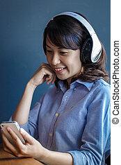 젊은 숙녀, 을 사용하여, smartphone, 와, 무선, 헤드폰