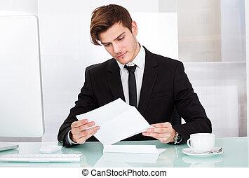종이를 읽고 있는 실업가
