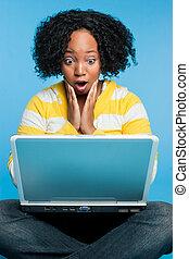 충격을 주는, 휴대용 개인 컴퓨터를 사용하고 있는 여성