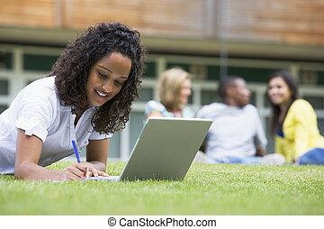 학생, 옥외, 통하고 있는, 잔디, 휴대용 개인 컴퓨터를 사용하는 것, 와, 다른, 학생, 에서, 배경,...