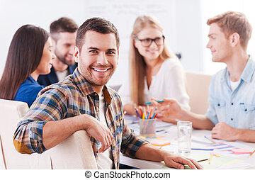 행복하다, 에, 이다, a, 부분의, 창조, team., 그룹, 의, 쾌활한, 실업가, 에서, 현명한 임시 노동자, 착용, 함께 앉아 있는 것, 테이블에서, 와..., 토론, 무엇인가, 동안, 잘생긴, 남자, 사진기를 보는, 와..., 미소