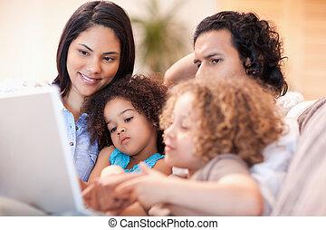 행복한 가족, 휴대용 개인 컴퓨터를 사용하는 것, 함께