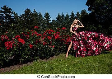 Hermosa mujer en el jardín con rosas rojas. Hermosa joven ...