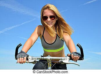 Blonde teenagerin auf fahrradtour.