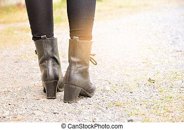 Piernas de mujer con botas altas de cuero negro, fondo blanco.