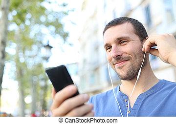 Der typ hört musik auf der straße. Vorderansicht eines