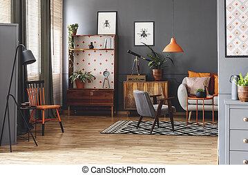 Einfaches wohnzimmer mit plakaten und schwarzer uhr an der