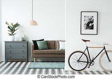 Fahrrad im grauen wohnzimmer. Fahrrad mit blauen rädern