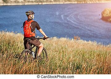 Junger mann fährt mountainbike auf der grünen wiese über dem