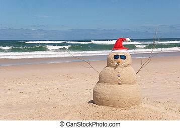 sandman on beach with santa hat and sunglasses snowman on