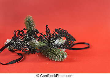 1 black lace mask on a fir branch on red background, Christmas decoration