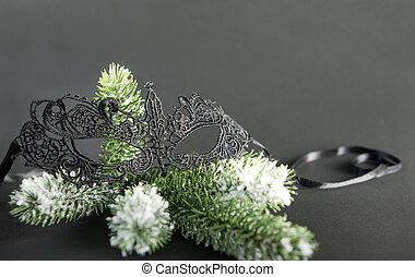 black lace masquerade mask on spruce branch on black background