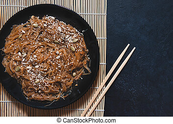 1 black plate of brown Chinese rice noodles funchosa with shiitake mushrooms and nut sauce, sesame seeds on a Mat on a dark background,