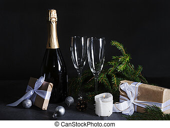 1 bottle of champagne, 2 glasses, fir branches in the dark on a black background, gift box with white ribbon, silver balls, candle,