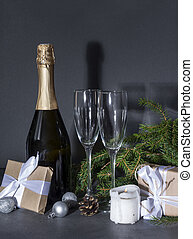 bottle of champagne, 2 glasses on the background of fir branches in the dark, gift box with a white ribbon, silver balls, candle, cone