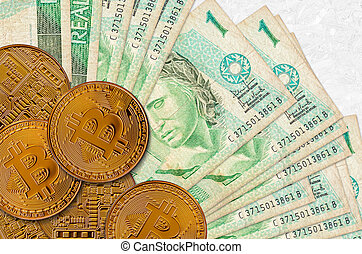 1 Brazilian real bills and golden bitcoins. Cryptocurrency investment concept. Crypto mining or trading