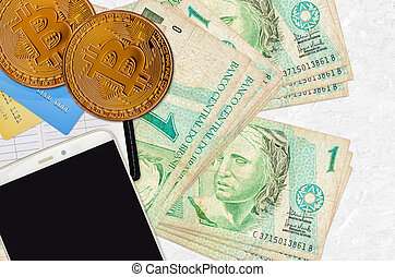 1 Brazilian real bills and golden bitcoins with smartphone and credit cards. Cryptocurrency investment concept. Crypto mining or trading