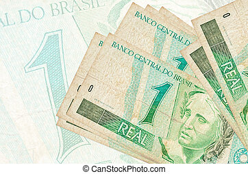 1 Brazilian real bills lies in stack on background of big semi-transparent banknote. Abstract presentation of national currency