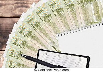 1 Chinese yuan bills fan and notepad with contact book and black pen. Concept of financial planning and business strategy