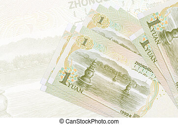 1 Chinese yuan bills lies in stack on background of big semi-transparent banknote. Abstract presentation of national currency