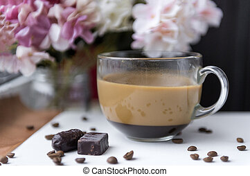 Cup of coffee with milk, 2 candies, coffee beans, flowers