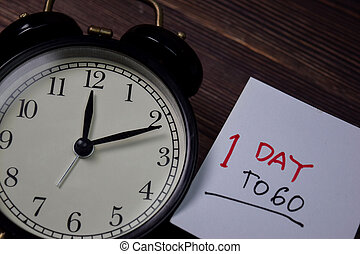 1 Day To Go write on sticky note isolated on wooden table.