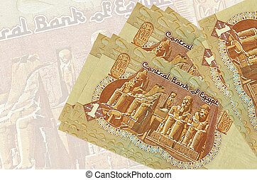 1 Egyptian pound bills lies in stack on background of big semi-transparent banknote. Abstract presentation of national currency