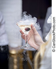 glass of champagne with a dry ice haze in hand