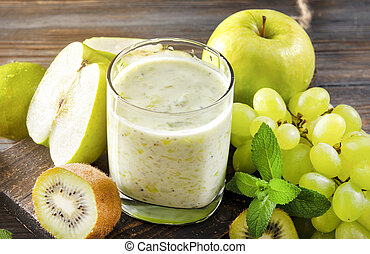 glass of natural yogurt with fresh kiwi, green grapes, Apple and mint on a wooden