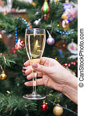 glass of sparkling wine in a woman's hand on the background of a decorated Christmas tree