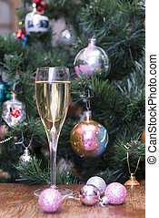 1 glass of sparkling wine, pink Christmas balls on the background of Christmas tree