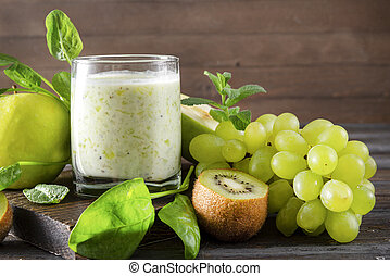 glass of  yogurt with fresh kiwi, Apple, green grapes,  spinach and mint on a wooden