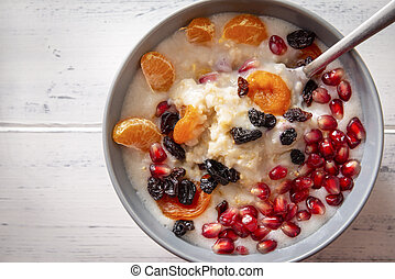 plate of oatmeal porridge with pieces of fruit on a white wooden background, top view,