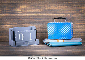 1 july wooden, square calendar. suitcase bag for traveling