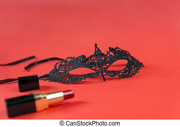 Lacy black mask, red lipstick on red background