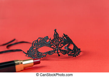 Lacy black mask, red lipstick with black case on red background