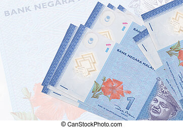 1 Malaysian ringgit bills lies in stack on background of big semi-transparent banknote. Abstract presentation of national currency