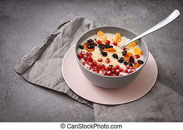 1 plate of oatmeal porridge with fruit slices, tangerine slices, raisins, dried apricots, pomegranate seeds on a gray