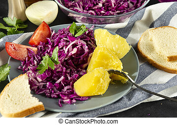 plate of red cabbage salad with greens, tomato boiled potatoes on a towel, a piece of bread, fork, onion on a black background, vegetable salad, closeup