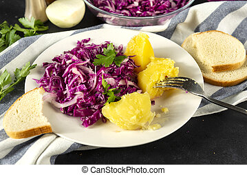 plate of red cabbage salad with greens, tomato boiled potatoes on a towel, a piece of bread, fork, onion on a black background
