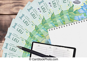 1 Romanian leu bills fan and notepad with contact book and black pen. Concept of financial planning and business strategy